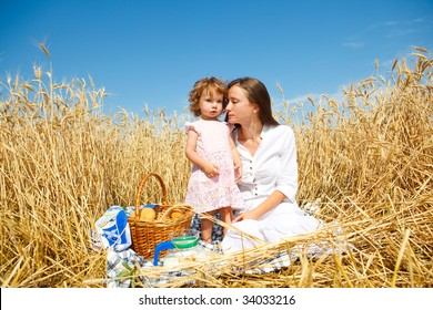 Tranquil scene of mother and daughter having breakfast  in field
