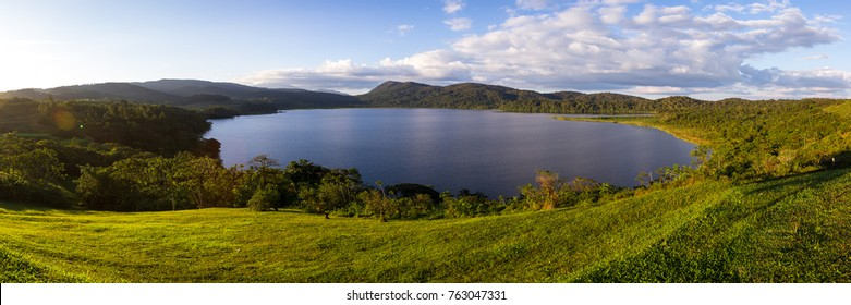 Tranquil scene with a warm sun glow from the setting sun lighting up the grassy areas surrounding Cote Lake in Costa Rica