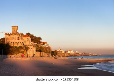 Tranquil scenery by the Atlantic Ocean, Tamariz Beach overlooked by a castle at sunset in resort town of Estoril in Portugal.
