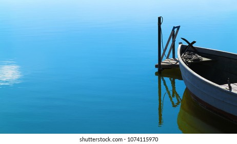 tranquil scenery with moored rowing boat in calm water and copy space