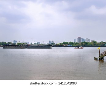 Tranquil Scenery of Small Tug Boat Towing Large Barge Ship in the River