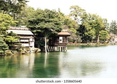Tranquil scenery of a traditional Japanese Building at a lake in Kenroku-en Garden park, Kanazawa, Japan