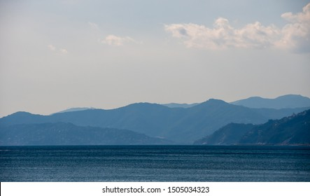 Tranquil seascape with foggy mountains and rosy sky. Misty landscape in the hazy weather