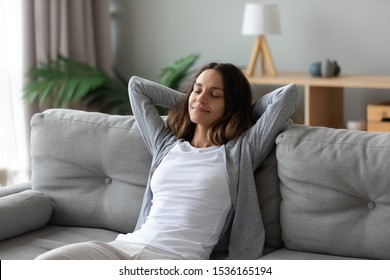 Tranquil smiling biracial millennial woman leaning on sofa, enjoying stress free weekend time at home. Mindful happy mixed race young girl relaxing in living room, meditating, visualizing future. - Shutterstock ID 1536165194