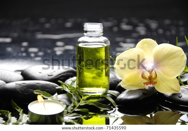 tranquil spa scene - massage oil and candle with black stones with green orchid