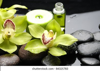 tranquil spa scene –massage oil and candle with green orchid