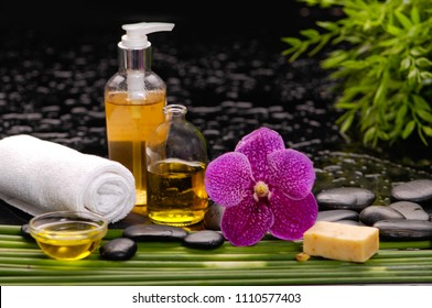 tranquil spa scene- pink orchid with towel, candle with ,green plant palm, bottle oil ,black stones
