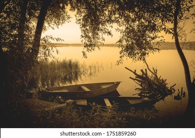 Tranquil summer morning scene with boats on river bank.Vintage photo landscape made with warm sepia filter.Beautiful calm summer landscape with golden retro colors.