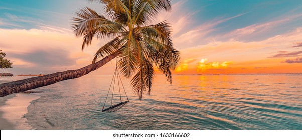 Tranquil summer vacation or holiday landscape. Tropical sunset beach view with palm over calm sea water and swing or hammock. Exotic nature view, inspirational and peaceful seascape reflection, sunset