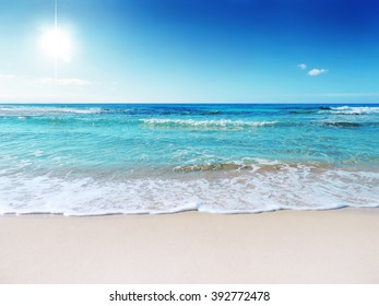 A tranquil sun and sea scene. The gently rolling waves of the sea roll in and out. The shot is taken on the white sands of a tropical beach. The water is a crystal-blue color.