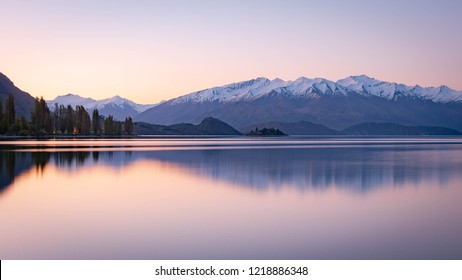 Tranquil sunrise moment at the Tekapo lake in New Zealand. Pink and purple from the sky gave a beautiful reflection on the water.