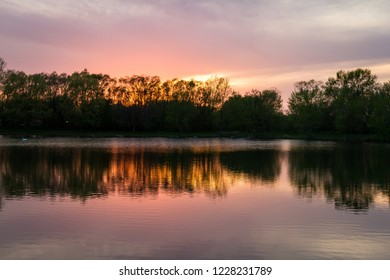 tranquil sunset reflecting on a pond with warm tones reflecting off the clouds and water