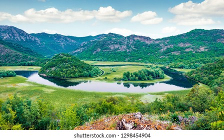 Tranquil waters of the Crnojevica river with strange sleeves stretched out among the mountain hills. Aerial view of meandering canyon near Skadar lake lacation, Montenegro, Europe.