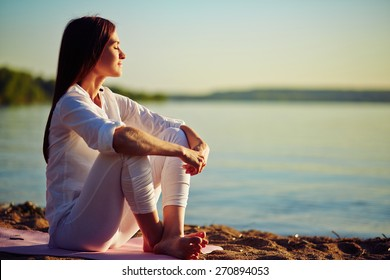 Tranquil young woman sitting on the beach - Shutterstock ID 270894053