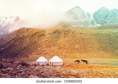 Tranquility of highlands. Clouds between the mountains and yurts with horses.