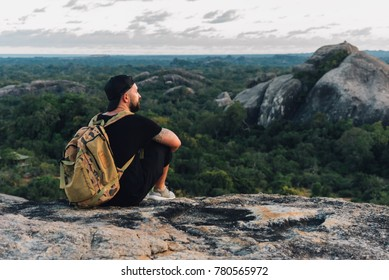 tranqul man in orange T-shirt sitting and look beautiful view on the big stone in the forest