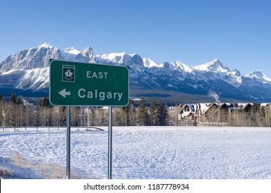 Trans Canada Highway sign pointing to east and Calgary, in the background the Rocky Mountains and the town of Canmore.