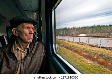 Trans Siberian Express, Siberia, Russia - March 20, 2018:  Old Russian passenger is watching outside from Trans Siberian Train in Siberia, Russia.