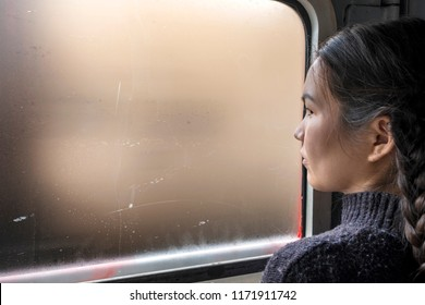 Trans Siberian Express, Siberia, Russia - March 20, 2018: Russian girl is watching outside from window in Trans Siberian Train. Siberia, Russia.