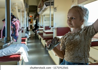 Trans Siberian Express, Siberia, Russia - March 20, 2018: Little Russan girl is playing with her baby in Trans Siberian Ekspress. Siberia, Russia.