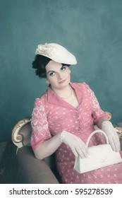 Trans woman retro 1920s fashion sitting on sofa with handbag.