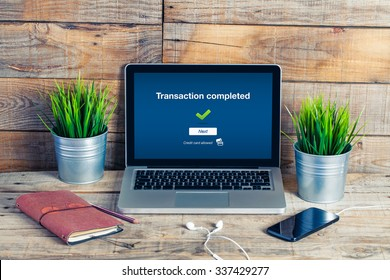 Transaction completed notification in a laptop screen. Wooden office desk with business stuff