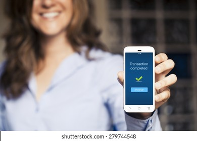 Transaction completed notification in a mobile phone screen. Woman showing her mobile phone.