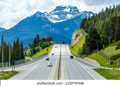 Trans-Canada Highway at Banff - A cloudy Spring day view of Trans-Canada Highway at exit to Banff Townsite, with massive Mt. Bourgeau standing high in background, Banff National Park, AB, Canada.