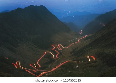 Transfagarasan road illuminated by the light of cars, road in the valley, Romania.