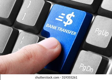 Transfering online. gesture of finger pressing Bank Transfer button on a computer keyboard