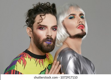 A transgender couple, 2 attractive male persons with beards and makeup on their faces, looking at the camera. The guy with a quiff touching the back of his partner in women's clothing and bob-cut wig.