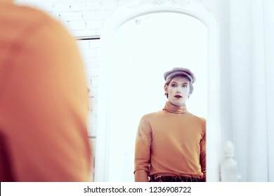 Transgender sad man. Transsexual man looking in his reflection in the mirror being fully-dressed and with make up on