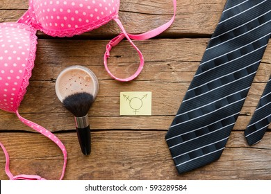 transgender symbol next to the bra and tie on a wooden background