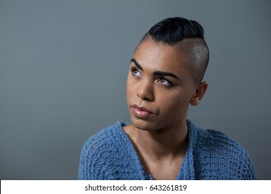 Transgender woman looking away while standing against gray background