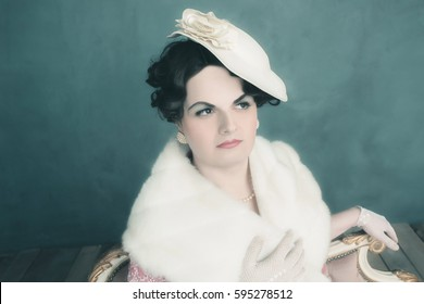 Transgender woman retro 1920s fashion sitting on sofa.