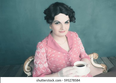 Transgender woman vintage 1920s fashion sitting on sofa holding cup of tea.