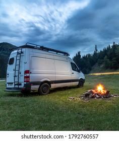 Transilvania/Romania- 01.08.2020: Van in the wild near a campfire and cloudy night sky