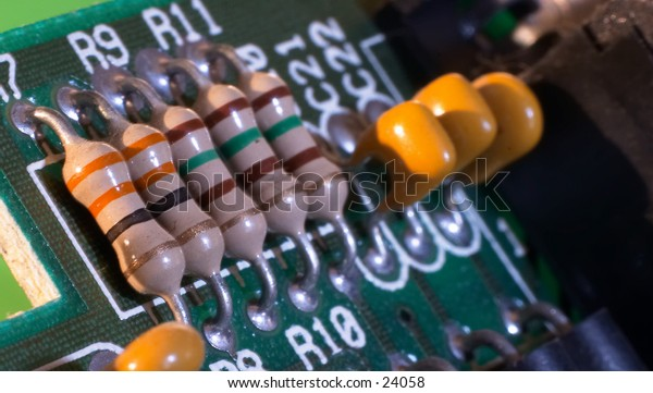 Transistors (foreground) and ? capacitors on a circuitboard from a 1989 286-model computer. Macro.