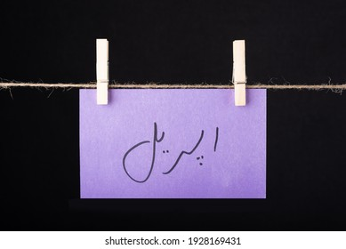 Translation April in urdu word written on a Purple color sticky note hanging with a wire on black background - Shutterstock ID 1928169431