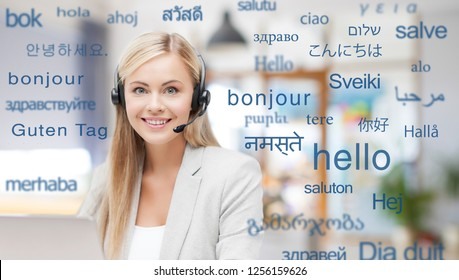 translation, business and technology concept - smiling female translator or operator in headset at office over greeting words in different foreign languages