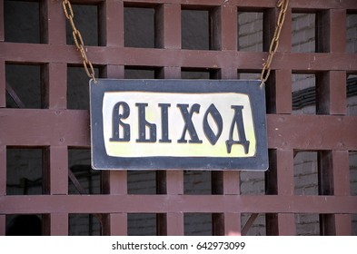 Translation: EXIT.  Sign on Russian language on a wooden lattice background
