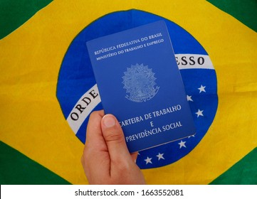 "Translation: ""Federative Republic of Brazil, Ministry of Labor. Work record booklet and Social Welfare"" / Young woman hand holding Brazilian work card (carteira de trabalho) over Brazilian flag."