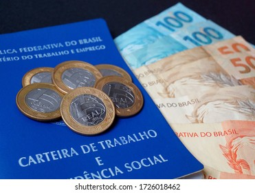 Translation: Federative Republic of Brazil, Ministry of Labor. / Brazilian Work Card (Carteira de Trabalho) and Brazilian money. Real banknotes and coins. Concept of economy, salary and savings.