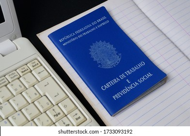 Translation: Federative Republic of Brazil, Ministry of Labor./ Brazilian Work Card (Carteira de Trabalho), notebook paper and laptop computer. Formal job. Concept of looking for a job on internet.