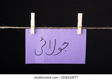 Translation July in urdu word written on a Purple color sticky note hanging with a wire on black background - Shutterstock ID 1928163977