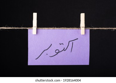 Translation October in urdu word written on a Purple color sticky note hanging with a wire on black background - Shutterstock ID 1928164004