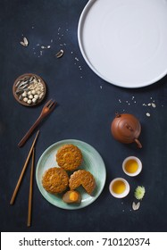 Translation on text appear in image: Mid-autumn. Conceptual flat lay mid-autumn festival moon cake food and drink on rustic blue background.