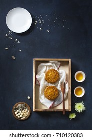 Translation on text appear in image: Mid-autumn. Conceptual flat lay mid-autumn festival moon cake food and drink on rustic dark blue background.