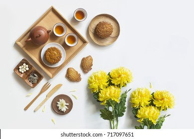 Translation on text appear in image: Mid-autumn, Lotus seed and Single egg yolk. Flat lay mid-autumn festival moon cake food and drink on white background.