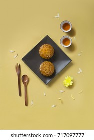 Translation on text appear in image: Lotus seed and Single egg yolk. Conceptual flat lay mid-autumn festival moon cake food and drink on gold colour background.